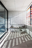 Venetian blind made of powder-coated aluminum as a contrast to the concrete walls and travertine tiles