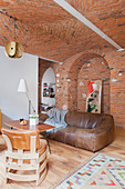 Designer leather chairs, coffee table and leather sofa in open-plan interior with brick ceiling, brick wall and partition wall