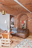 Designer-Lederstühle, Coffeetable und Ledersofa in offenem Wohnraum mit Ziegeldecke und teilweise Ziegelwand