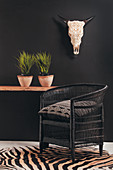 Black wicker armchair on zebra-patterned rug against black wall