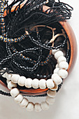 Various black and white necklaces in wooden bowl