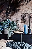Vase mit Hortensien und Eucalyptuszweigen, Schale, Krug un Tischlampe auf Sideboard