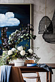 Bouquet of white dahlias and branches of leaves in vases on dining table, pendant lights made of spiral wire above