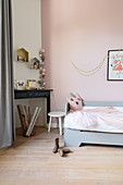 Pale grey bed and disused fireplace in girl's bedroom with pink wall