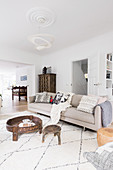 Pale sofa with scatter cushions, coffee table and antique wooden cupboard in open-plan interior