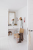Antique chair, mirror and ladder in front of small washstand in white bathroom