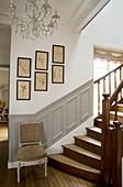 Stuhl vor der Treppe an der Wand mit Kassettenverkleidung und Herbarium