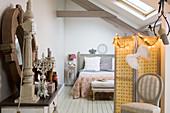 Bett hinter dem Paravent im Schlafzimmer unter der Dachschräge