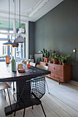 Long dining table, classic chairs and houseplants on sideboard in dining room with dark wall and white wooden floor