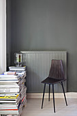 Black chair and stacked magazines in front of radiator on dark wall