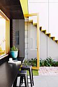 Um das Küchenfenster gewickelter Rahmen aus perforiertem Metall dient als Vordach und als Ablage