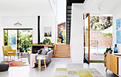 Bright, open living room in retro style with stairs and terrace access