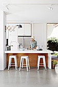 Kitchen counter with bar stool, woman behind the counter