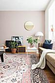 Polstersofa, Beistelltisch, Stehlampe und Wandspiegel in hellem Wohnzimmer mit Teppich