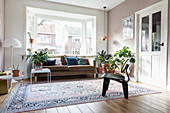 Cushions on sofa in window bay, houseplants and rug in bright living room
