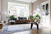 Polstersofa mit Kissen vor Erker und Zimmerpflanzen in hellem Wohnzimmer mit Teppich