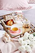 Frühstückstablett mit Tee, Croissant und Grusskarte auf Bett, Blumen und kleines Geschenk