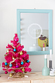 Hot pink Christmas tree next to mirror etched with Christmas greeting