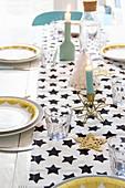 Tischläufer mit Sternenmuster auf weihnachtlich gedecktem Tisch