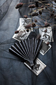 Paper fan and black and white pictures on black fabric