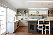 Grey-painted island counter with base cabinets and wooden worksurface in white fitted kitchen