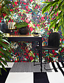 Black and gilt table in front of colourful leaf-patterned wallpaper