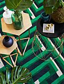 Verschiedene Beistelltische auf einem grün gemusterten Teppich