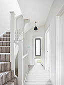 White hallway and stairwell flooded with light
