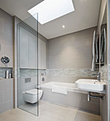 Bathroom in shades of grey with skylight and floor-level shower