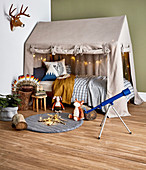 Fabric house over the bed in the children's room with a natural theme