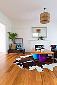 Colorful buckets under coffee table on animal fur rug in front of fireplace in living room