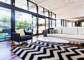 Carpet with black and white zig-zag pattern, coffee table, couch and armchair in front of glass front in open living room