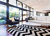 Teppich mit schwarz-weißem Zig-Zag-Muster, Coffeetable, Couch und Sessel vor Glasfront in offenem Wohnraum