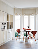 Designerstühle um einen runden Esstisch im Erker der Wohnküche