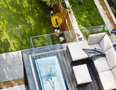 Sofa on roof terrace with glass balustrade and view of garden