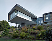 Modern architect-designed house with storey projecting over slope