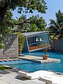 Slanted cube-shaped architect-designed house next to swimming pool