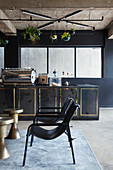 Black chairs and small metallic tables in front of black counter in vintage-style bar