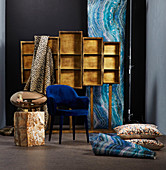 Luxurious wallpaper and fabrics, floor cushions, blue chair and shiny metallic lamp