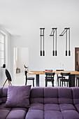 Blick vom Sofa auf den Esstisch mit schwarzen Stühlen und Leuchten
