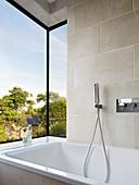 Bathtub in modern bay window with view of garden