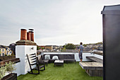 Man standing on roof terrace with city view