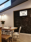 Illuminated panel on chalkboard wall in dining room with glass room
