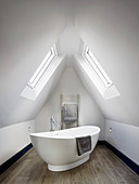 Free-standing oval bathtub in bathroom in gable room