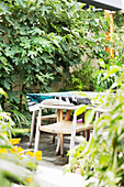 Wooden chairs at the table with oilcloth tablecloth in the garden