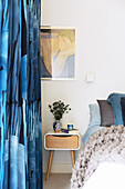 Blue patterned curtains next to the bed with a modern bedside table