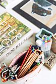 Töpferschale mit Stiften auf dem Tisch mit Büchern