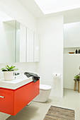 Red vanity unit as a color accent in the modern bathroom