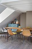 Schalenstühle am schlanken Holztisch unterm Dach
