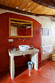 Concrete washstand with countertop sink in bathroom with red-painted floor and wall